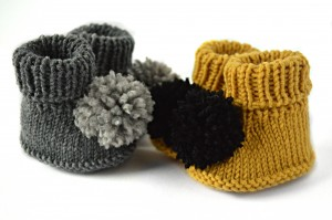 Knitted baby booties with pom pom